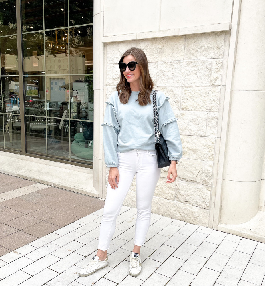 woman in white jeans and blue ruffled sleeve sweatshirt