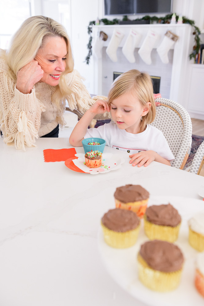 grandmother with toddler boy decorated cupcake
