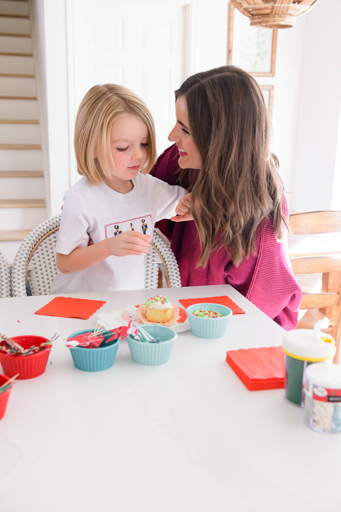 mom with toddler boy decorating cupcake