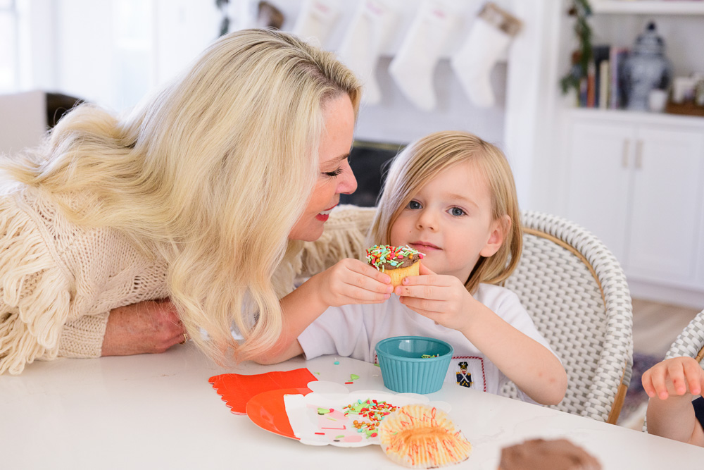 grandmother with toddler boy eating holiday decorated cupcake