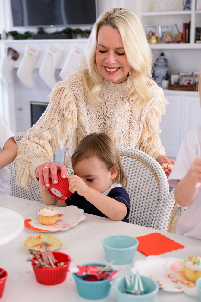grandmother with baby boy decorating holiday cupcakes
