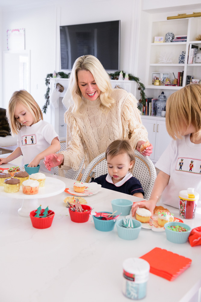 grandmother with three toddler boys decorating holiday cupcakes