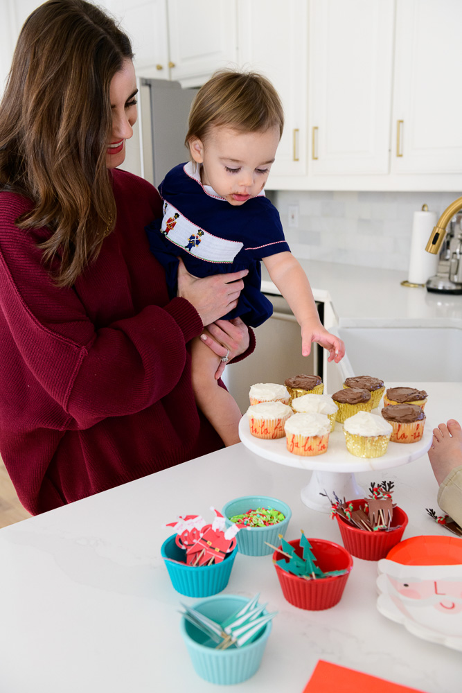 mom holding baby reaching for cupcake