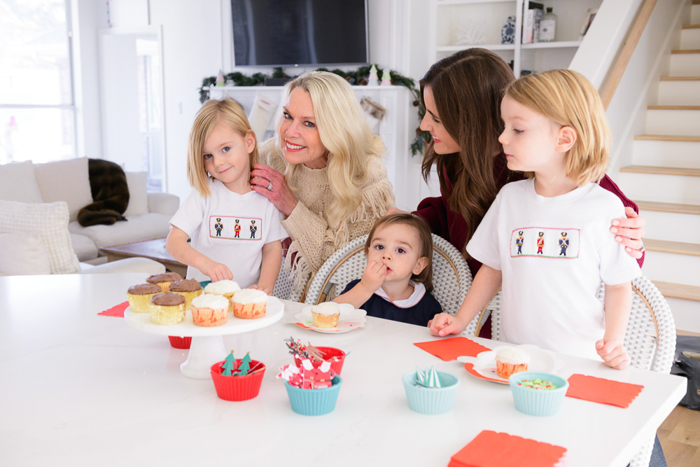 mom and grandmother with three toddler boys decorating cupcakes