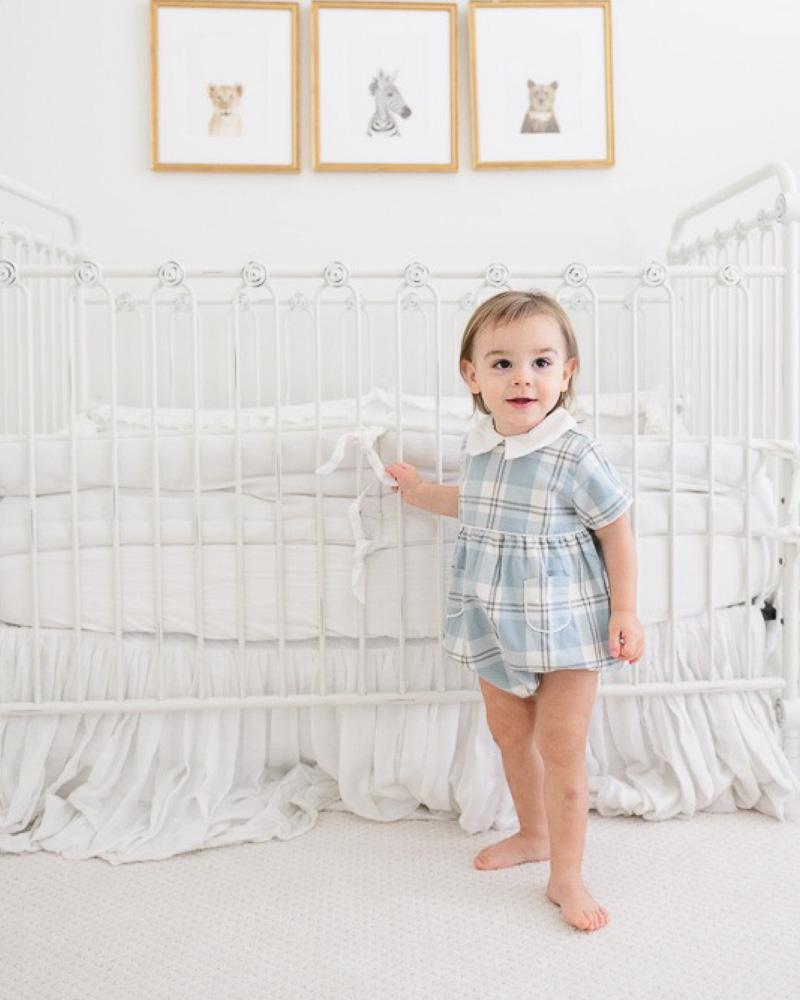 toddler boy standing by crib