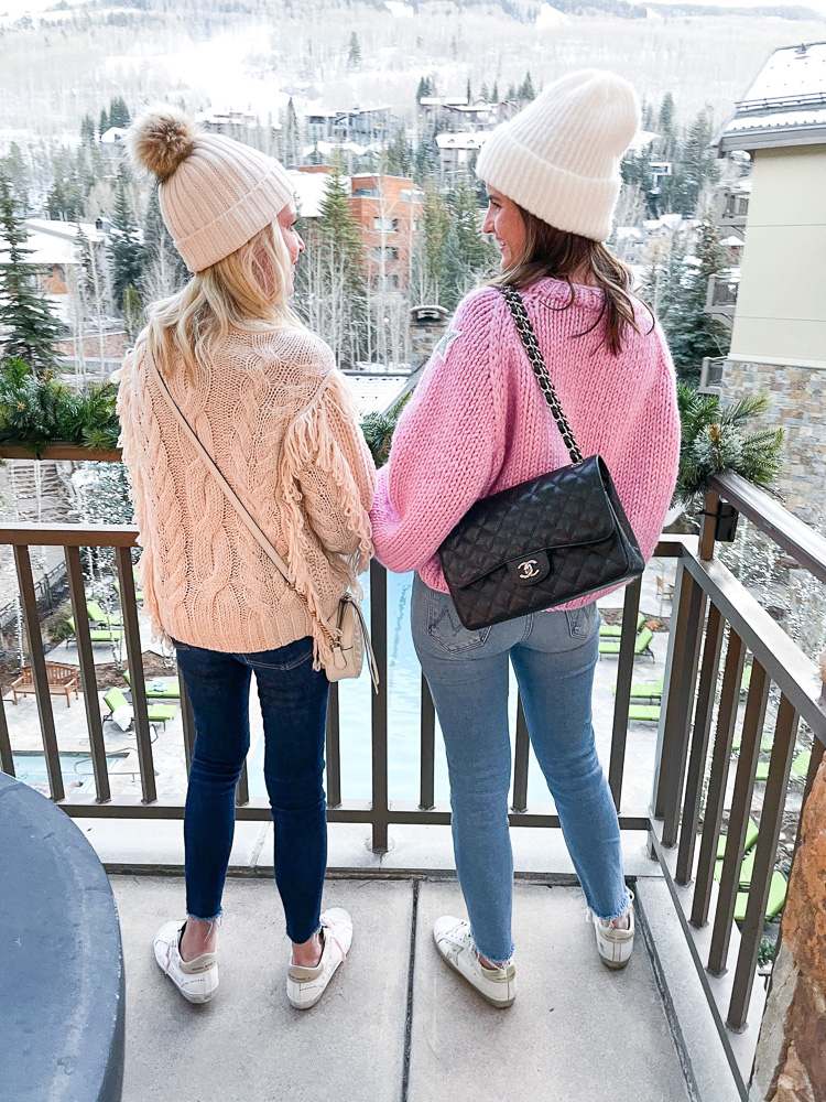 two women in sweaters and beanies in front of snow covered mountain