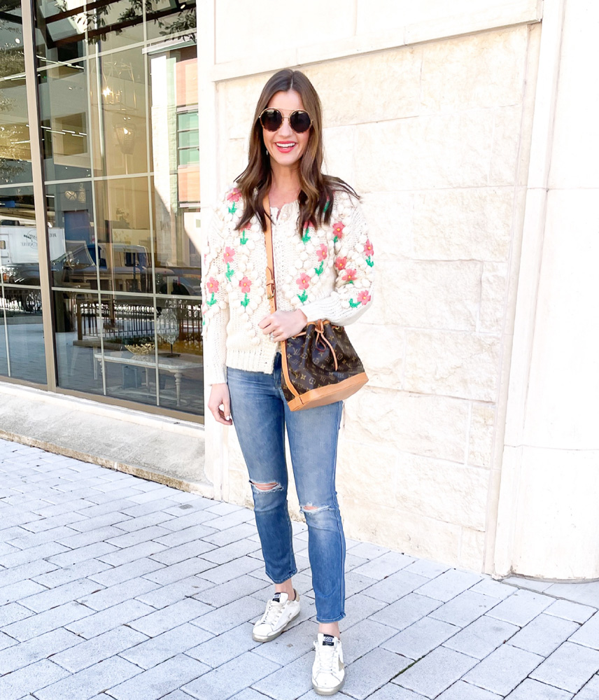 woman wearing floral caridagan louis vuitton handbag golden goose sneakers