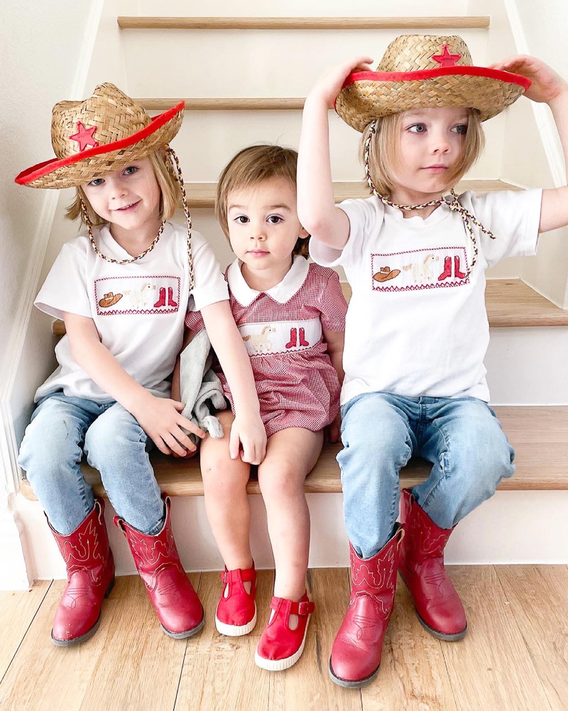 three toddler brothers sitting on stairs cowboy hats and boots
