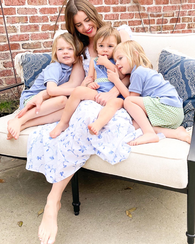 mom snuggling on love seat with three young sons