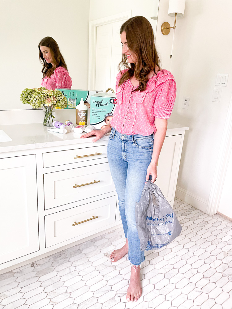 woman standing in bathroom with personal care products