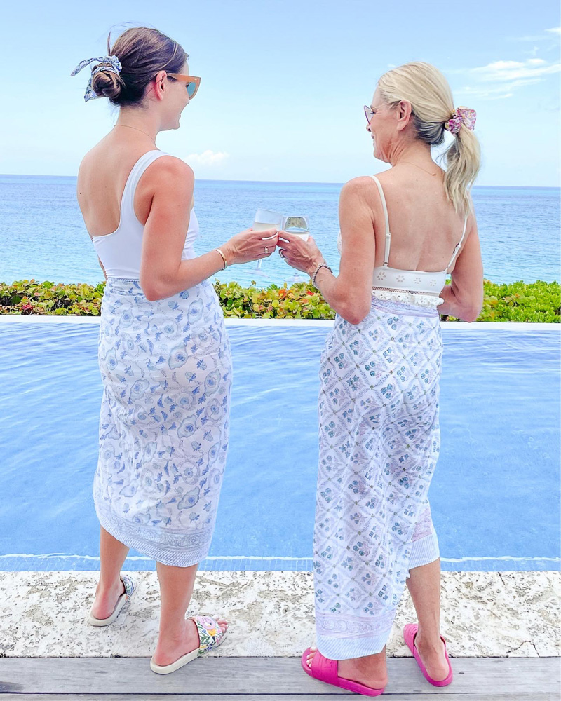 two women in coverups making a toast poolside