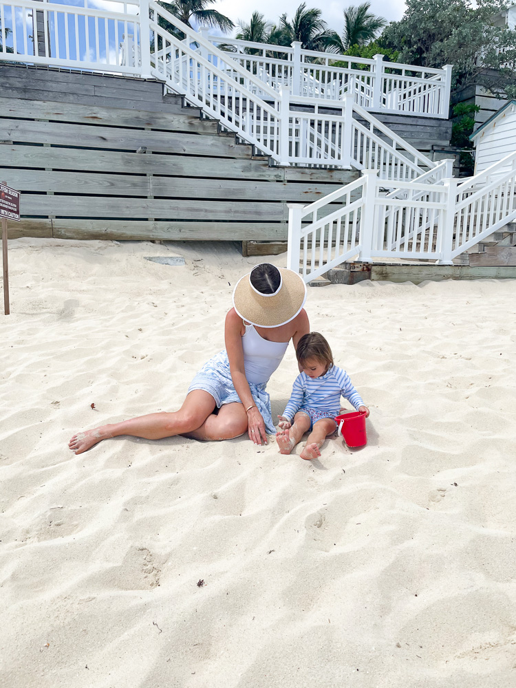 mom and toddler sitting on beach
