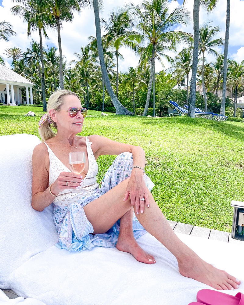 woman sitting poolside with rose wine