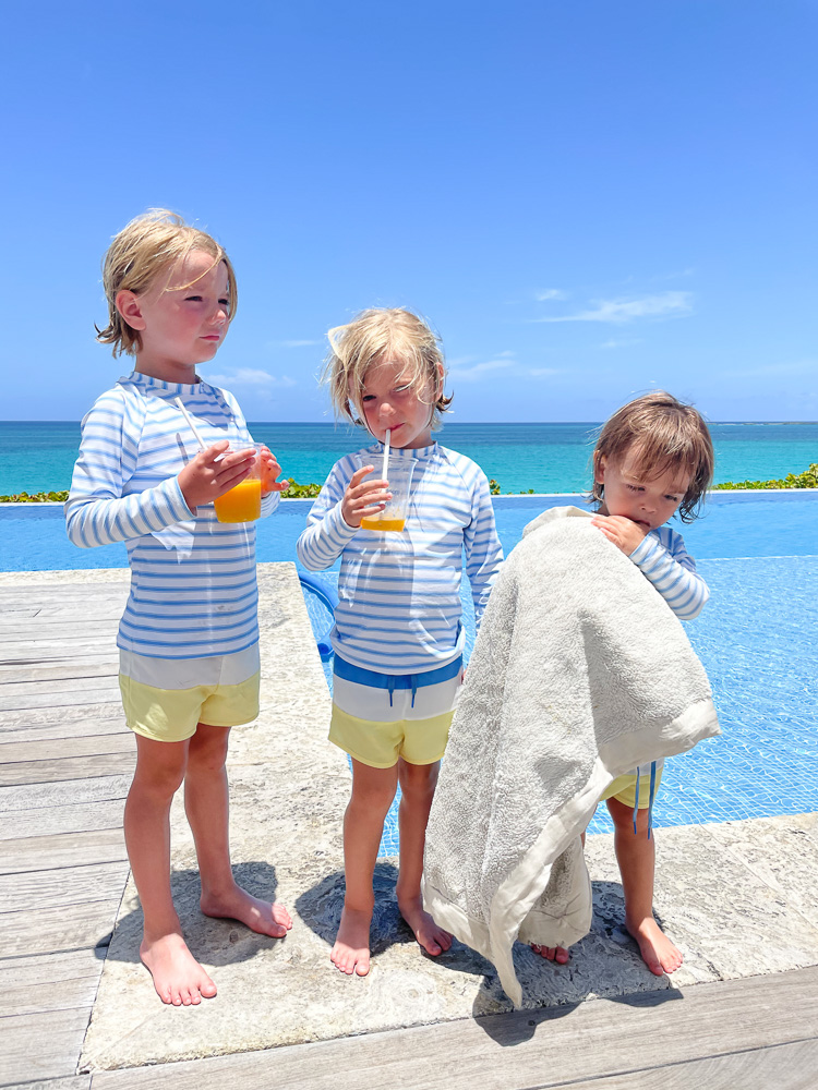 three toddler brothers in matching swimwear poolside