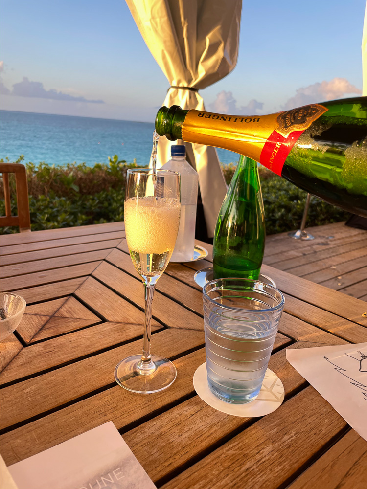 pouring champagne with view over ocean