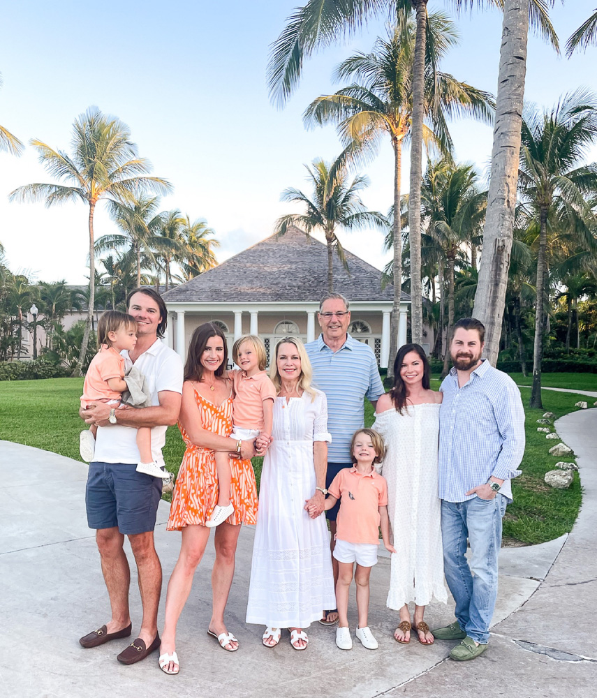 family group gathered under palm trees