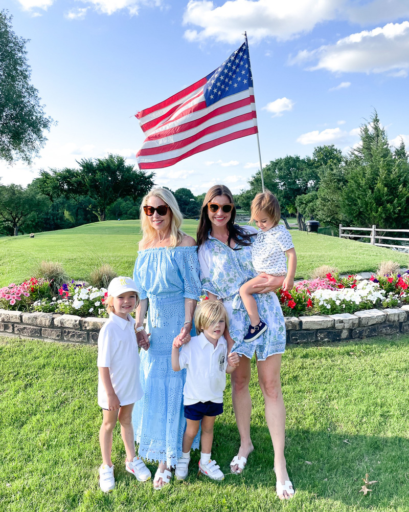 two women with three toddler brothers by American flag