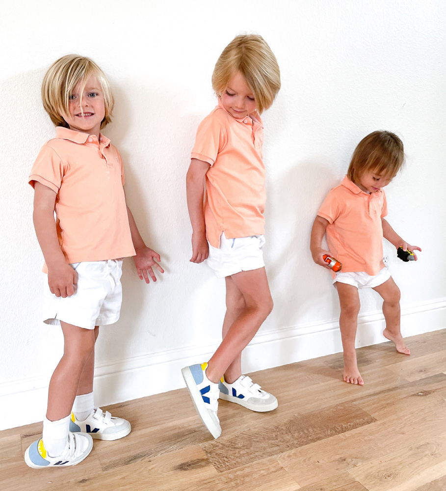 three brothers dressed in matching orange polo shirts and white shorts