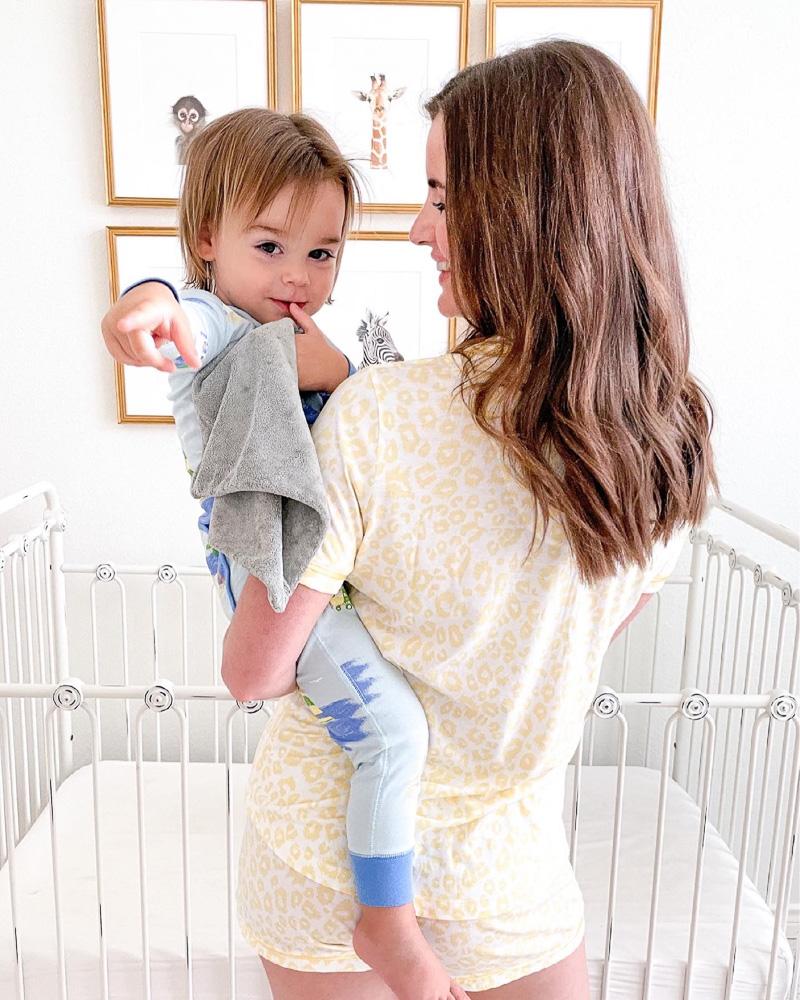 mom holding baby next to crib