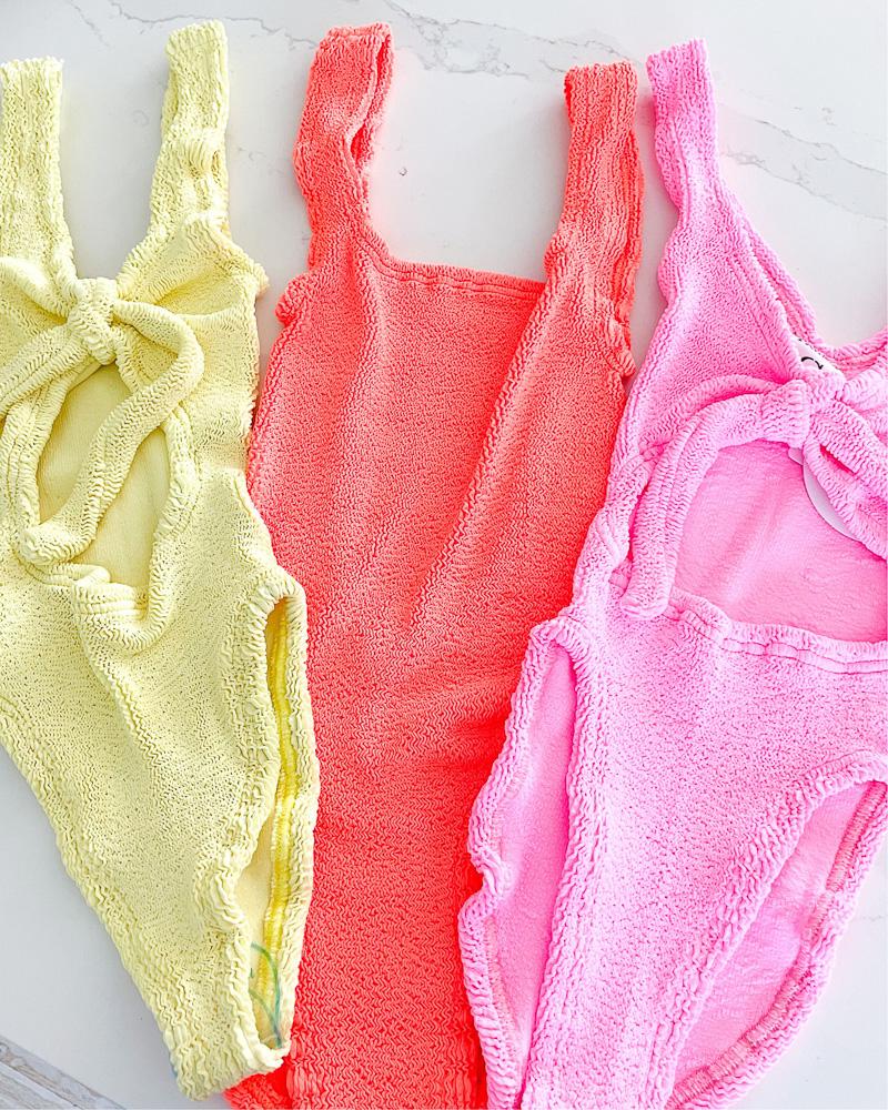 three swim suits in pink yellow and orange