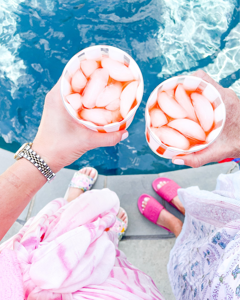 toasting with drinks over pool