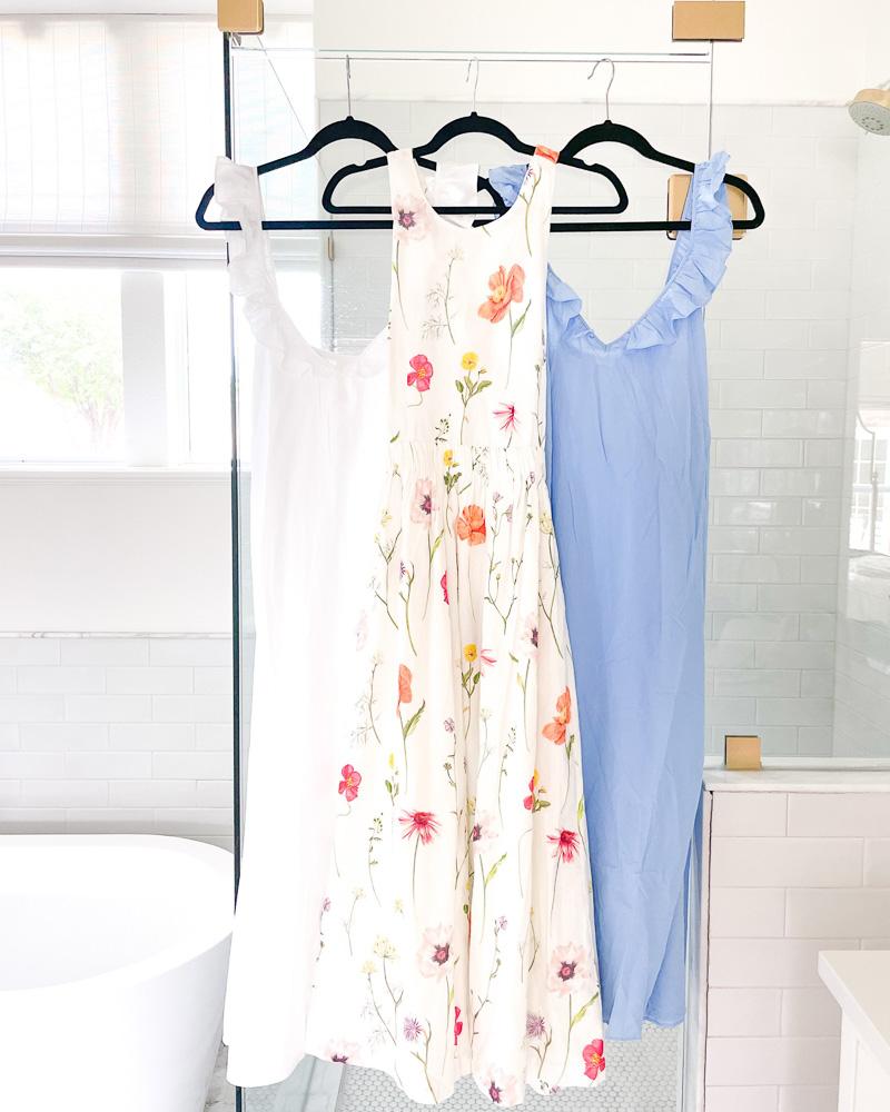 three summer dresses hanging on shower door