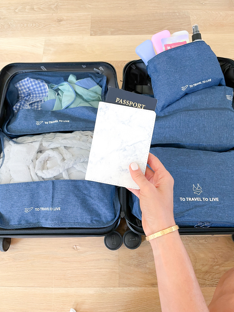 holding passport cover over packing cubes in suitcase