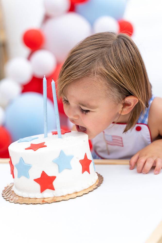 toddler boy biting into birthday cake