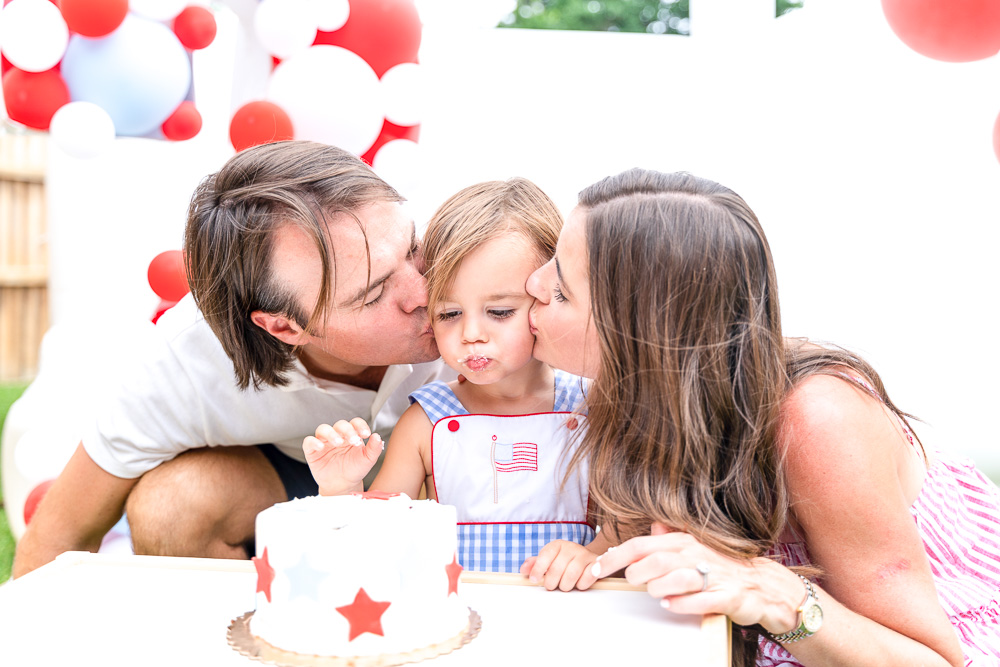 mom and dad kissing toddler boy with birthday cake