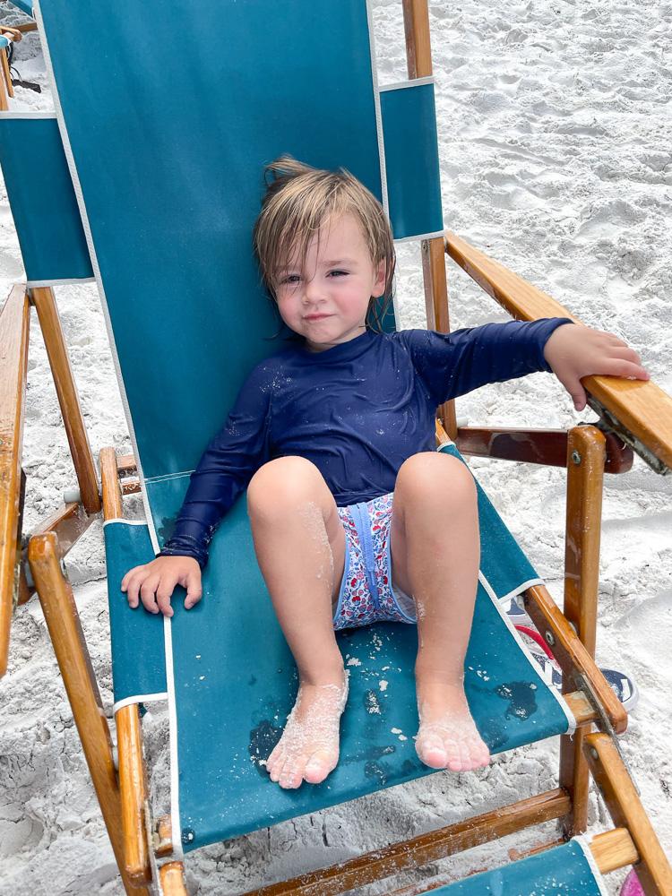 toddler boy sitting in beach chair