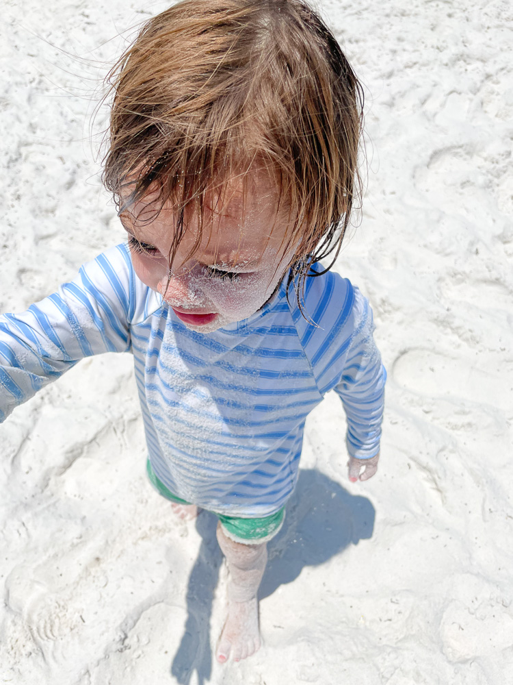toddler boy covered in sand at the beach