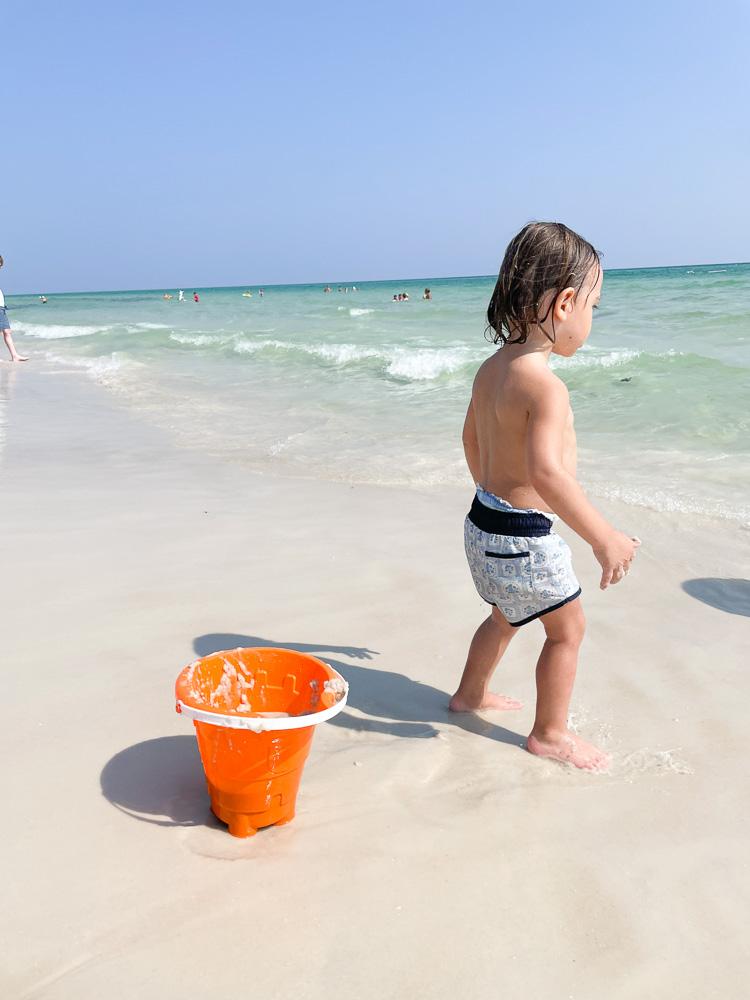 toddler boy at the beach with orange bucket