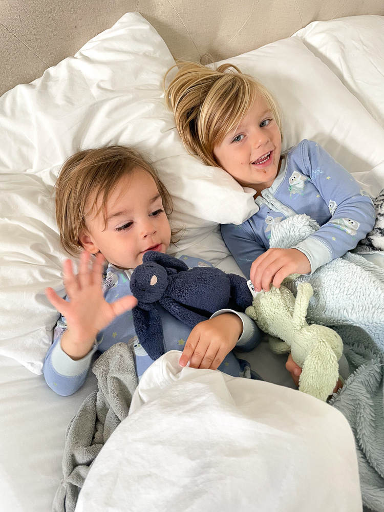 two toddler brothers snuggling in bed