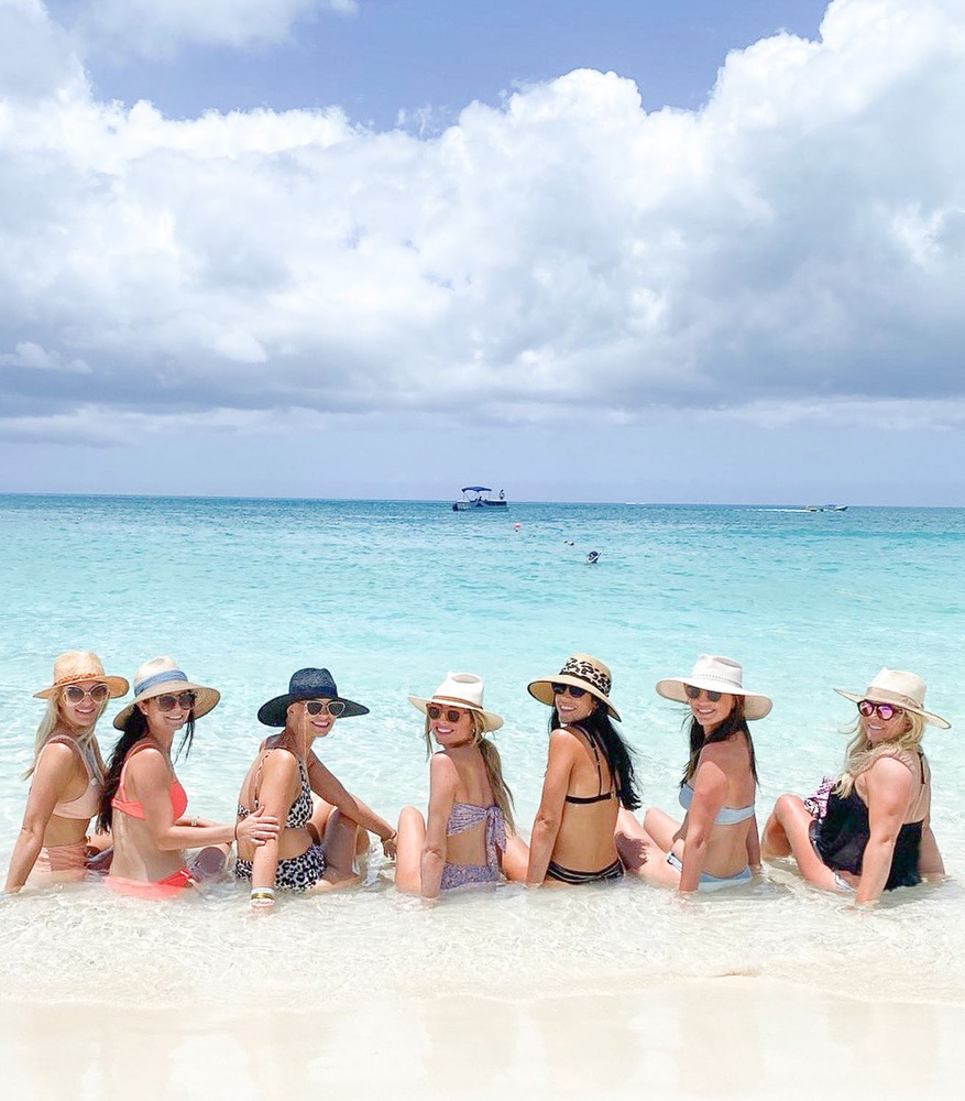 group of qwomen sitting in the ocean with sun hats looking back