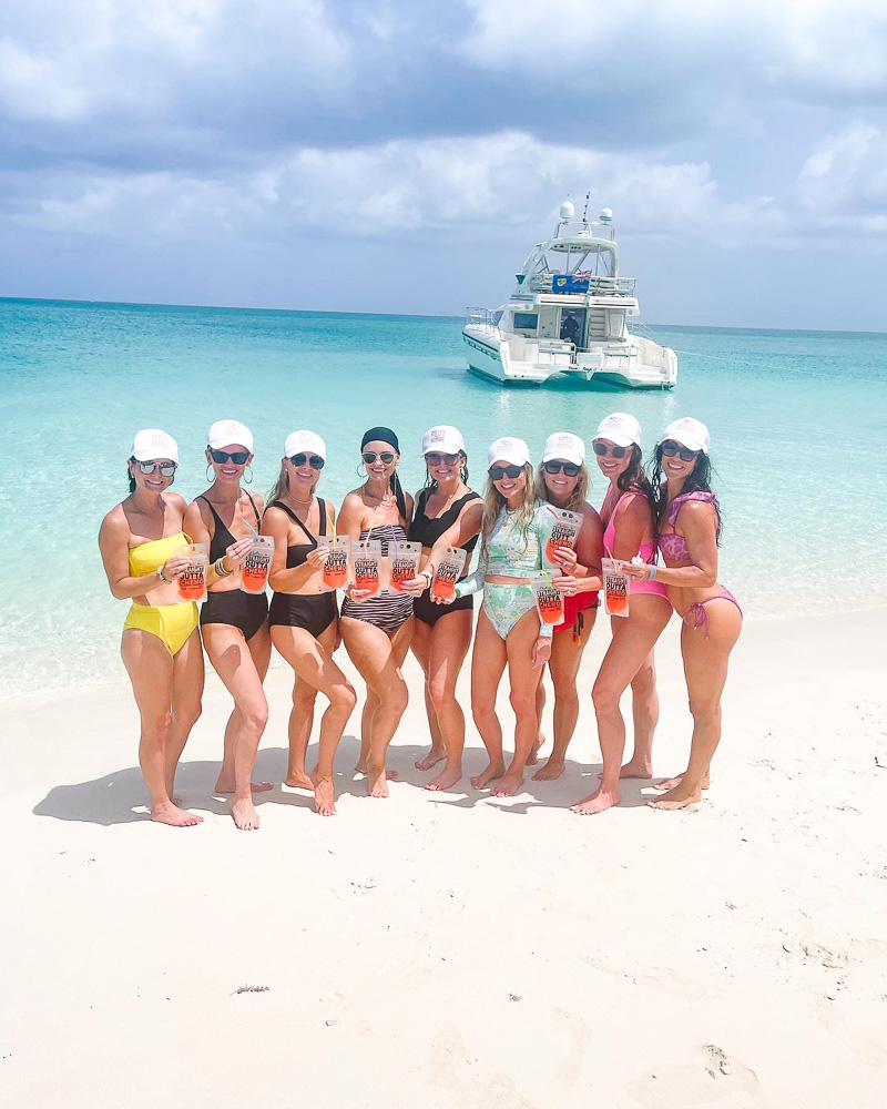 group of women in swim suits standing on the beach with drinks