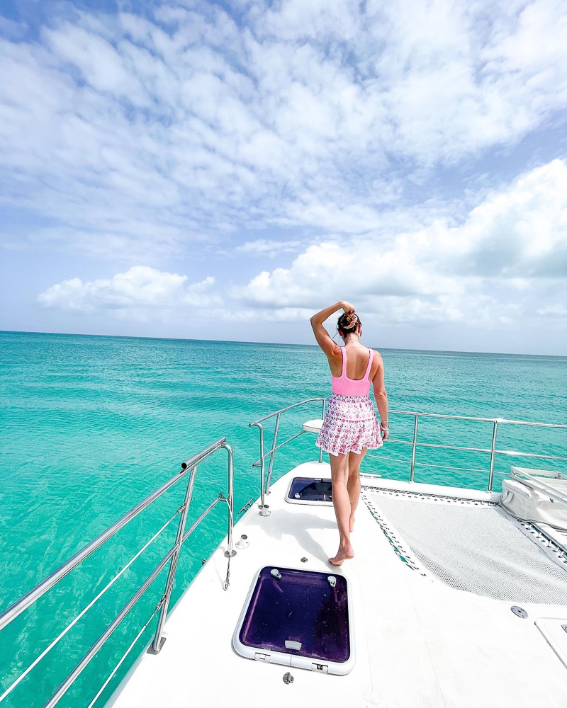 woman in swim suit and coverup on boat deck at sea