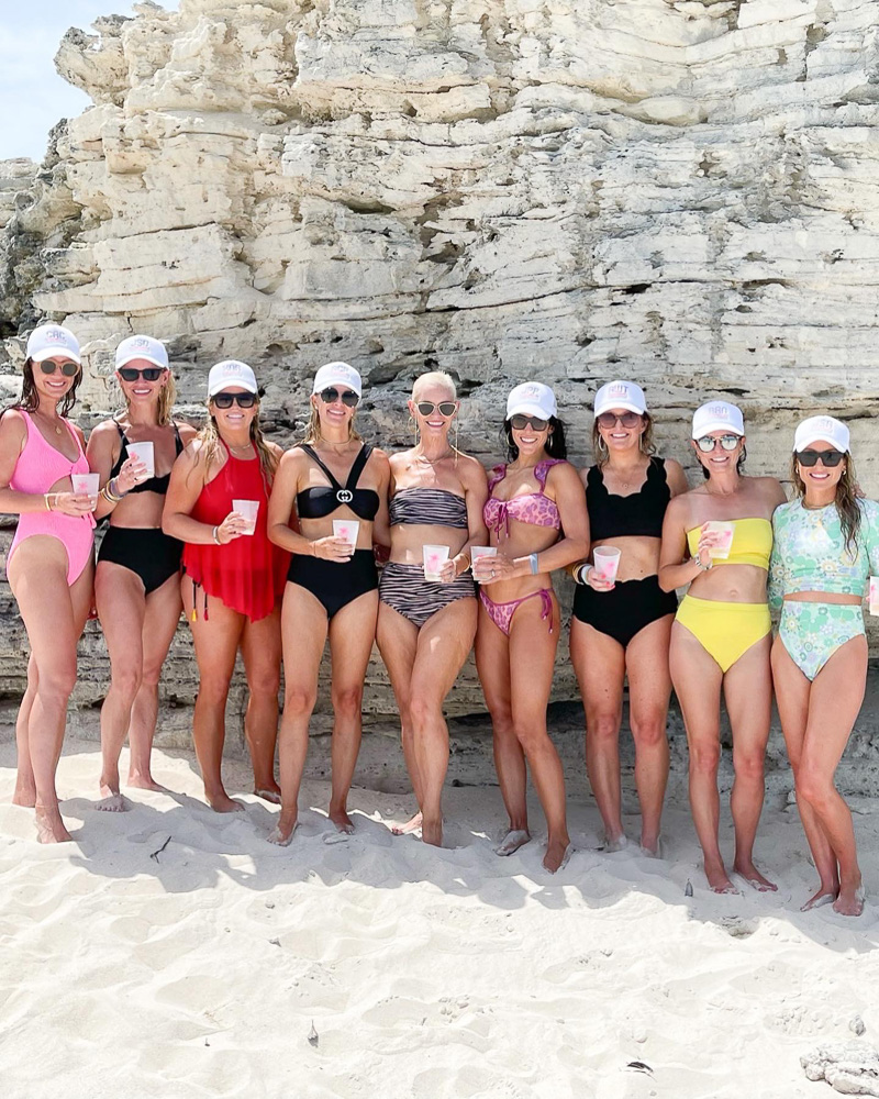 group of women in swim suits on the beach
