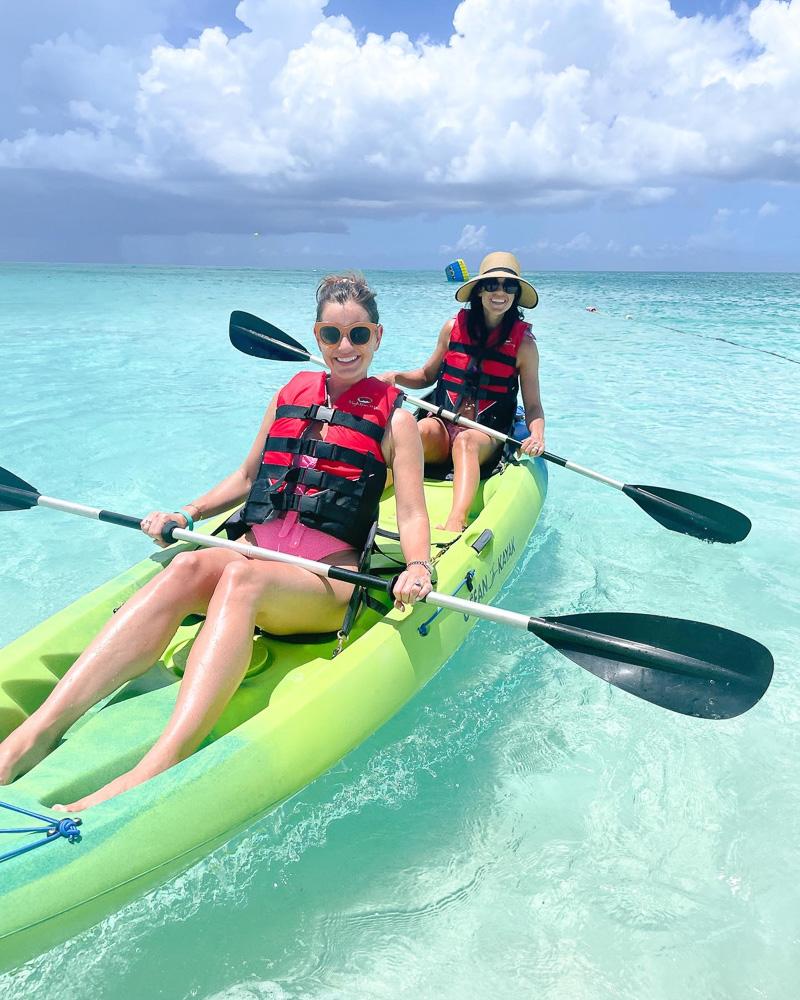 two women kayaking in clear blue ocean water