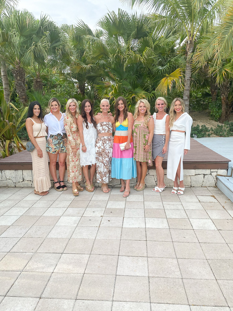 group of women dressed for dinner palm trees background