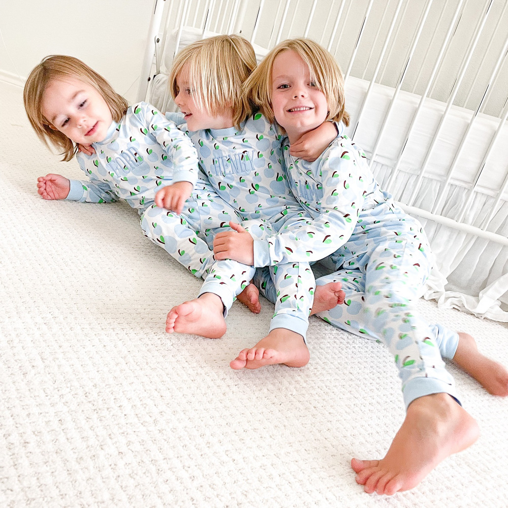three toddler brothers in matching pajamas hugging on floor