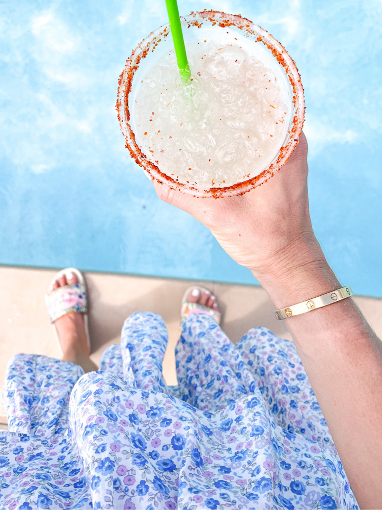 holding a margarita over swimming pool