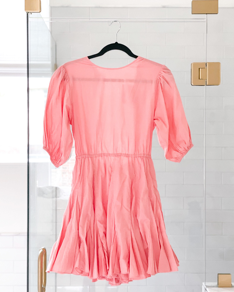 coral puff sleeve mini dress hanging on shower
