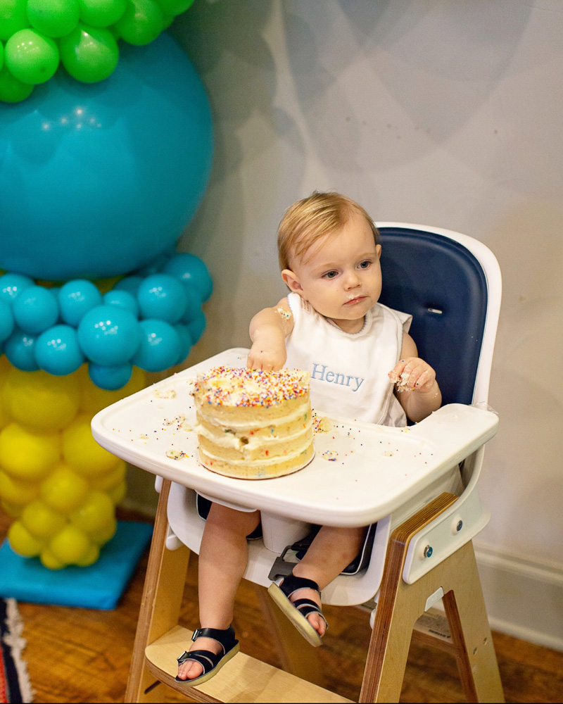 baby boy in high chair with smash cake and balloons