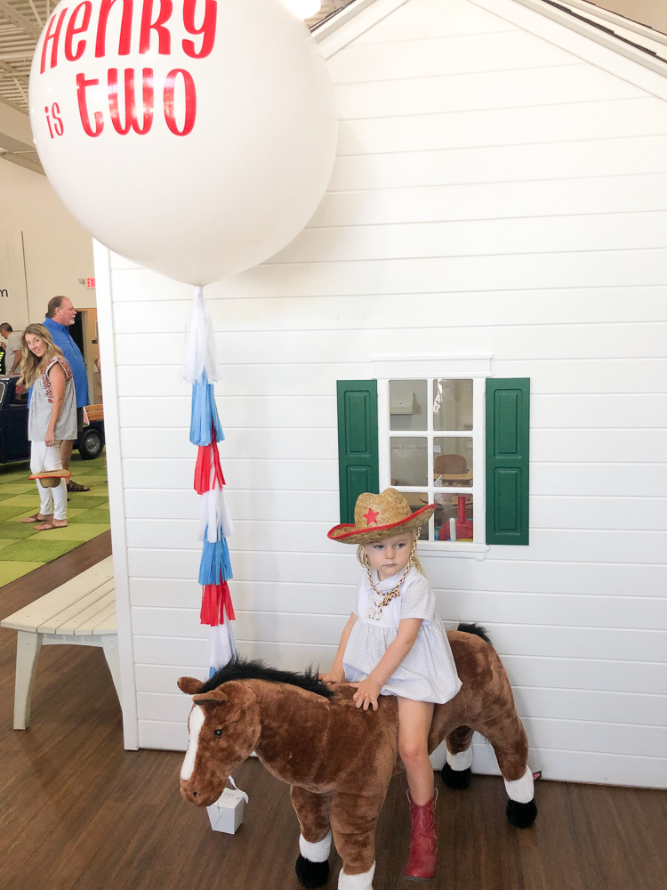 toddler oby on toy pony with hat and boots and balloon saying henry is two