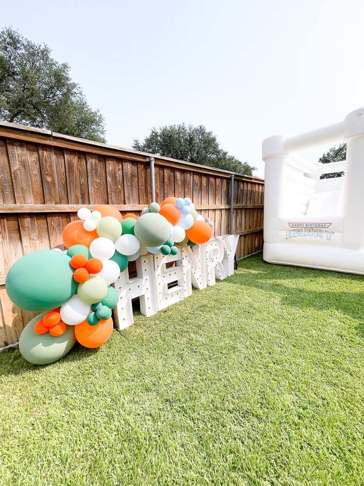 henry marquee sign with balloon garland and white bounce house