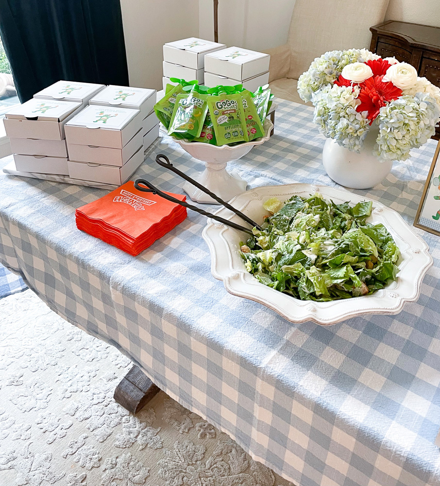 table set with blue and white gingham tablecloth large salad bowl mini white pizza boxes and blue and orange floral bouquet
