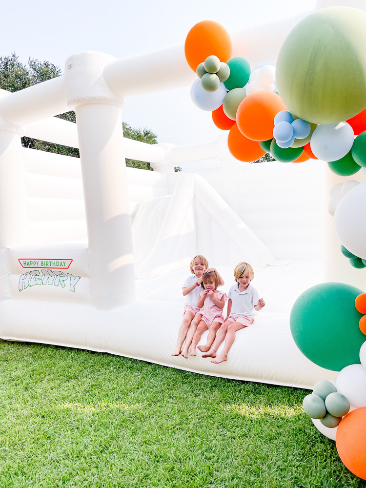 three young brothers sitting on white bounce house with colorful balloon garland