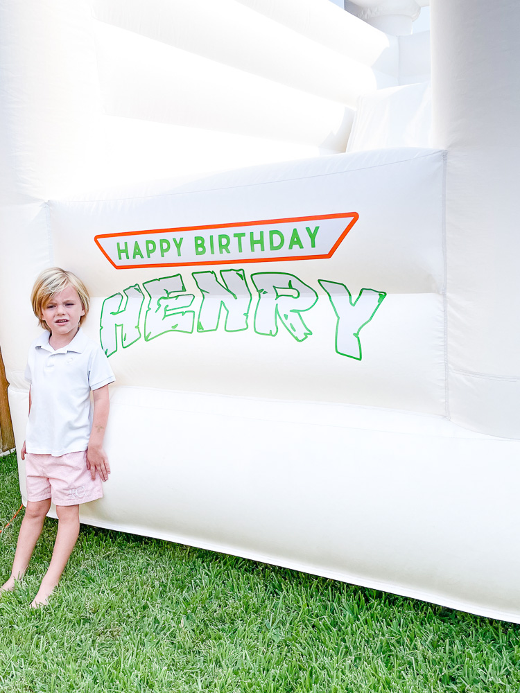 white bounce with custom happy birthday decal and small boy