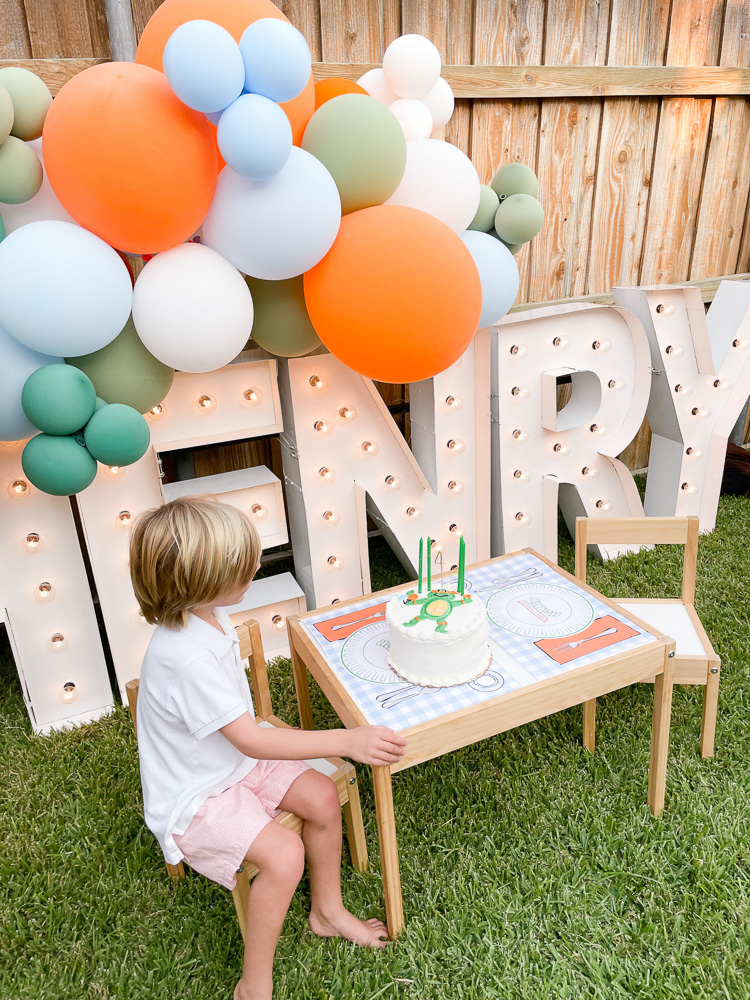 young boy sitting at kids table with birthday cake henry marquee lights and ballon garland