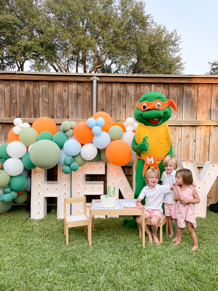 three young brothers sitting in front of henry marquee lights with balloon garland and teenage mutant ninja turtle character